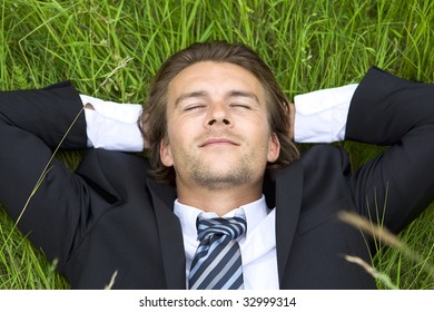 Well-dressed young businessman is resting in a field