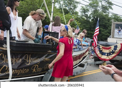 Wellfleet, Massachusetts, USA-July 4, 2014: Man shucking oysters on a float in the Wellfleet 4th of July Parade in Wellfleet, Massachusetts.