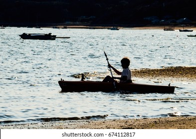 Wellfleet, USA - July 30, 2014: Young boy pulling kayak boat from sea in Cape Cod