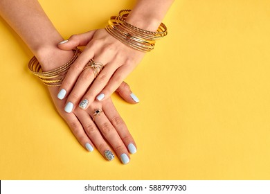 Well-groomed female hands with gold jewelery. Gently blue manicure with crystals on a yellow background.
