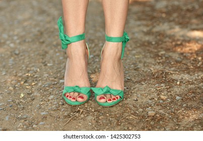 Well-groomed female legs in summer sandals with heels. Green lace-up sandals. Luxury vintage sandals on the long legs of the girl.