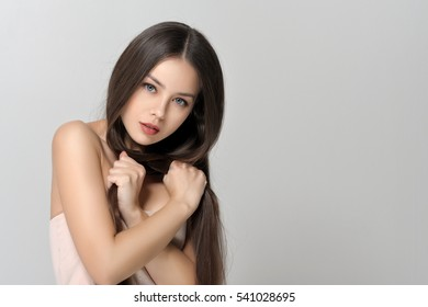 Well-groomed long hair. Beautiful woman with bare shoulders has a clean well-groomed skin and long straight hair. Close-up portrait against a light gray background.