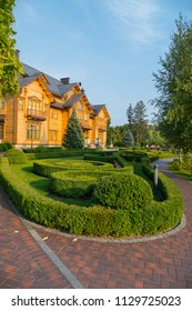 well-groomed park with landscape design, green lawns and figured shrubs in front of a large wooden cottage under a light blue sky. residence of Yanukovych Museum of Corruption of Ukraine Mezhyhirya