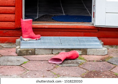 Wellies lying in the entrance of the wooden house.