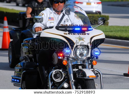 WELLINGTON, FL - November 11, 2017: Scene from the Wellington Veteran's Day parade on a sunny Saturday morning shows a Palm Beach County Sheriff motorcyle unit