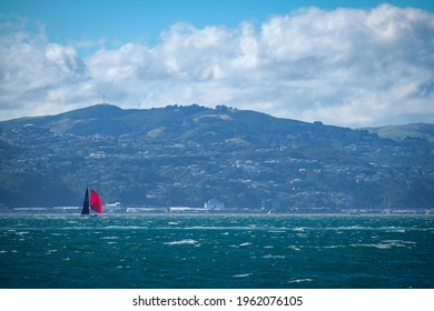 Wellington Harbour, New Zealand 25th April 2021. Yacht with red sail