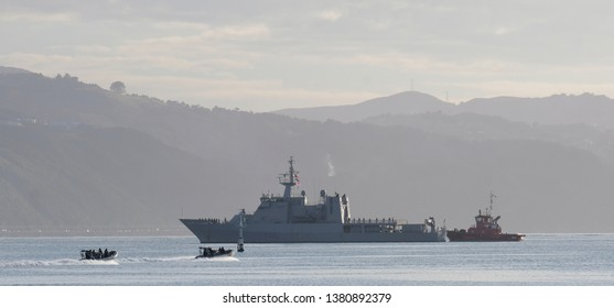Wellington Harbour, New Zealand - 29th March 2019. HMNZS Wellington being maneuvered by a tug boat.