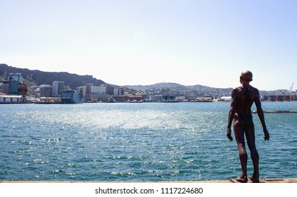 Wellington, New Zealand - 13 February  2016: Wellington Harbour on a summer day with Max Patte's iconic  'Solace in the Wind' statue in the foreground situated on the wharf outside Te Papa Museum.