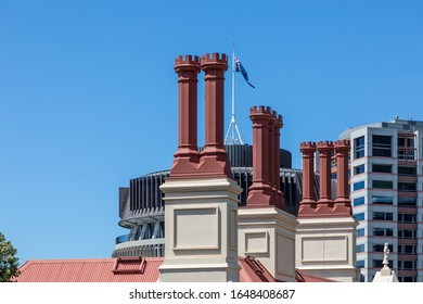 """Wellington, New Zealand - 28 December 2019: The red chimneys of the New Zealand Parliamentary Library,  designed in Gothic revival style and completed in 1899. In the background the """"Beehive"""""""