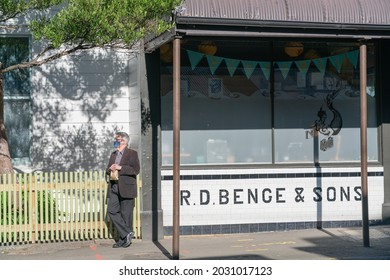 Wellington New Zealand - July 31 2021; One man well dressed wearing face mask to protett against covid-19 stands leaning against yellow picked fence in sun beside old butcher shop with tiled facade