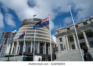 WELLINGTON NEW ZEALAND - OCTOBER 2; Flags flutter in front New Zealand Government buildings, House neo classical style House of Parliament with Beehive behind October 2 2018 Wellington New Zealand
