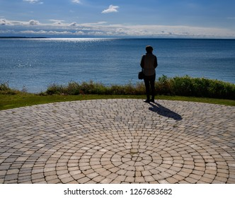 Wellington, Ontario, Canada - September 29, 2017: Woman visitor on patio at Wellington Farmers Market at shore of Lake Ontario with Sandbanks Provincial Park in Prince Edward County   w/ model release