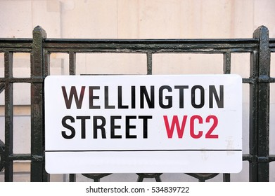 Wellington street, road or street sign attached on metal fence in London, England, UK