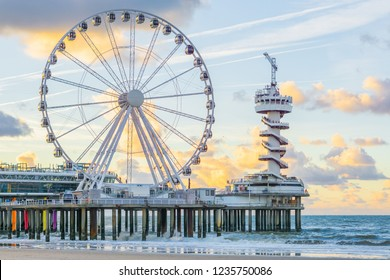 The well-known pier jetty of scheveningen beach the Netherlands with bungy jump tower and ferris wheel viewing on the ocean with waves