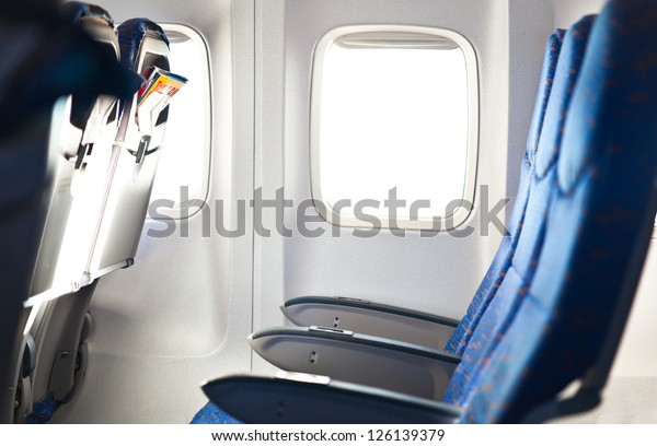Well-lit empty airplane interior with window and blue seat