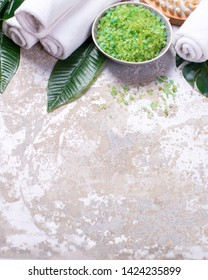 Wellnes spa  border. Bowl with green  sea salt, towels, massage tool, tropical leaves  on grey textured background. Spa concept. Selective focus. Place for text. Verticaal image.