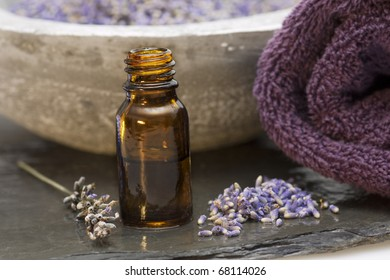 Wellness care products lavender oil and a towel on grey background