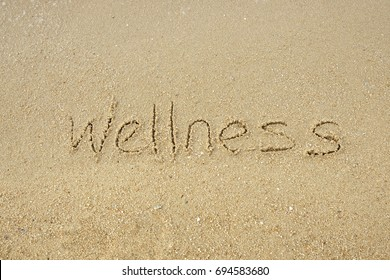 Wellness concept. The word Wellness written on sand.