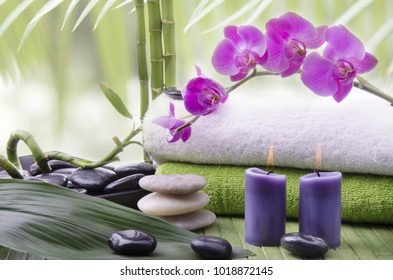 wellness environment with close-up of some bamboo stalks, aromatic candles, Stones for massage and beautiful purple orchid flowers.