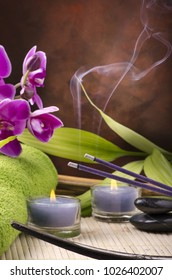 Wellness environment with massage stones, candles and incense sticks flavored in the foreground