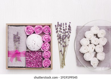 Wellness gift box with lavender flowers and lavender aroma, bath bomb, sea salt, bath roses, cotton grey towel. Homemade present for woman, mother on white table.