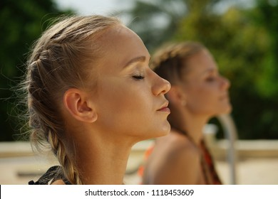 Wellness girls by yoga and breathing exercises outdoors