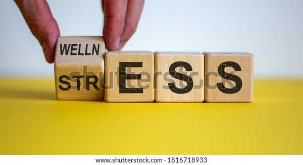 Wellness instead of stress. Hand turns a cube and changes the word 'stress' to 'wellness'. Beautiful yellow table, white background. Concept. Copy space.