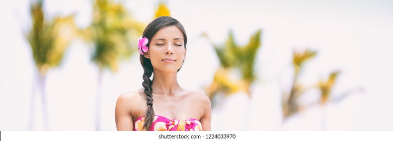 Wellness meditation Asian woman at spa resort meditating on Hawaii beach - relaxation, well-being healthy lifestyle.