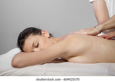 Wellness and relaxation, beautiful brunette woman relaxing on a stretcher receiving a therapeutic massage from hands of a professional masseuse