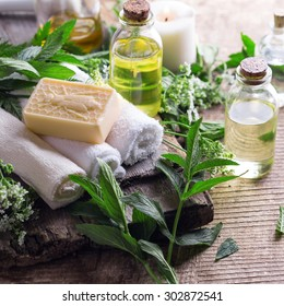 Wellness setting. Essential aroma oil, towels, soap on aged  wooden background. Selective focus. Square image.