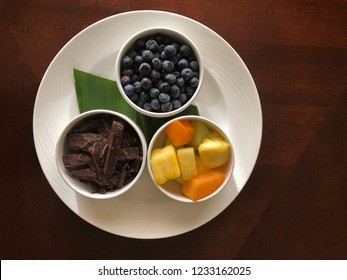 Wellness Snack: dark chocolate, blueberries, pineapples, and cantaloupes chunks on white platter adorned with a banana leaf