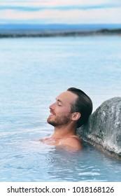 Wellness spa handsome man relaxing enjoying natural geothermal hot spring in outdoor Iceland nature. Reykjavik tourist nordic travel.