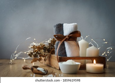 Wellness and spa items on a serving tray with a string of lights. Rustic style, towels, tealight.