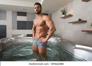 Wellness Spa - Man Flexing Muscles in Hot Tub Whirlpool Jacuzzi Indoors at Luxury Resort Spa Retreat - Handsome Young Male Model Standing Strong in Water Near Pool on Travel Vacation Holiday