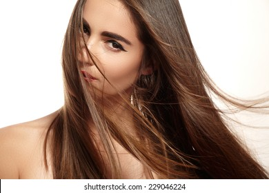 Wellness and spa. Sensual woman model with windswept flying dark hair on white background. Shiny long health hairstyle. Beauty and haircare