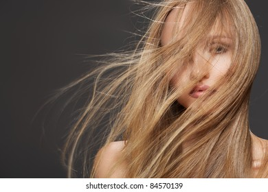 Wellness and spa. Sensual woman model with winswept flying dark blond hair on gray background. Shiny long health hairstyle. Beauty and haircare