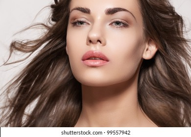 Wellness and spa. Sensual woman model with windswept flying brunette hair on light gray background. Shiny long health hairstyle. Beauty and haircare. Natural fashion make-up