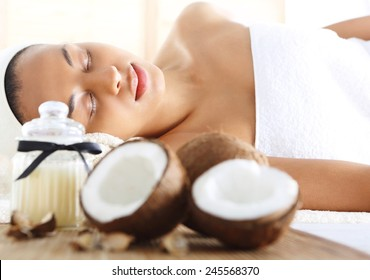 Wellness & spa treatment with coconut oil, feminine relaxation. Figure of a woman in the office of the spa during surgery care.