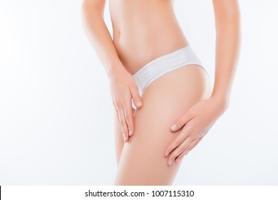 Wellness wellbeing purity freshness concept. Cropped close up photo of skinny slim slender attractive fit woman's thighs wearing white underpants gently touching soft fresh skin isolated on background