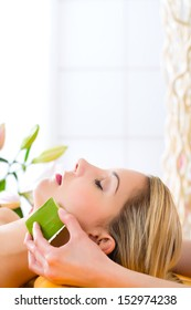 Wellness - woman receiving head or face massage whit aloe Vera in spa