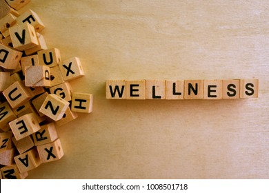Wellness word cube on wood background ,English language learning concept
