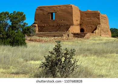 Well-preserved walls of a Spanish mission church built in 1717 in Pecos, New Mexico, with native cactus, grass, and trees