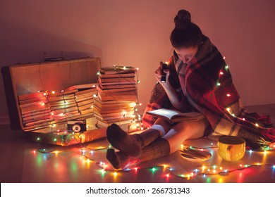 Well-read girl at home in Christmas lights. Night exciting reading by book lover