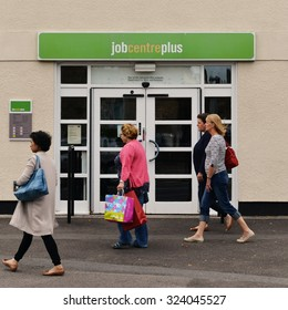 WELLS - AUG 30: People walk past a JobCentre Plus unemployment office in the city centre on Aug 30, 2014 in Wells, UK. The modern welfare state in the UK was founded on the Beveridge Report of 1942.