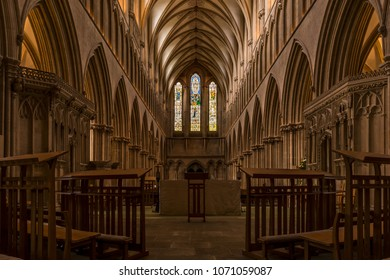 Wells Cathedral, Somerset, England - October 7, 2014: Interior stone arches, architecture and stained glass windows of historic Well Cathedral.