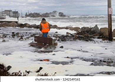 Wells, Maine, USA: December 18th, 2017: Storm waves flood a coastal road bringing with it rocks and damage.  A town worker walks through the damage.