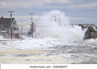 Wells, Maine, USA: February 3, 2018: A storm wave crashes over two telephone poles and the roof of a beach front house in wells Maine during high tide causing massive flooding.
