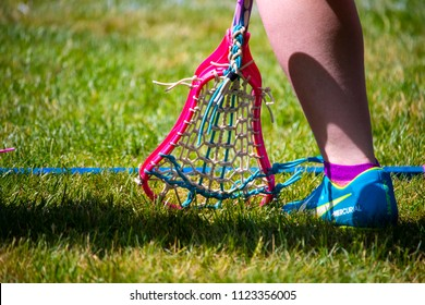 "Wells, Maine, USA: June 15, 2018: A closeup shot of a lacrosse stick next to a youth wearing a Nike cleat shoe against a grass background. The concept is the Nike slogan of ""just do it."""