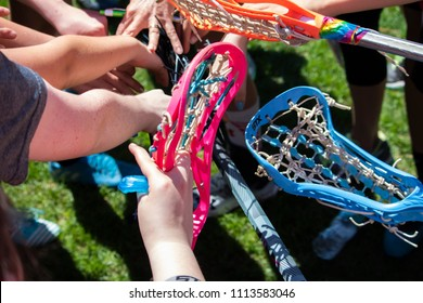 Wells, Maine, USA; June 4, 2018: A closeup shot of lacrosse players using their sticks and hands to form a circle to show teamwork and bonding before a game.  The concept is unity.