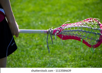 Wells, Maine, USA: June 4, 2018: A closeup shot of a lacrosse player's hand holding a lacrosse stick with a grass field out of focus in the background.